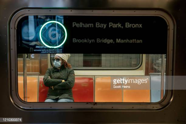 A commuter wears a face mask while riding a subway train on April 17 2020 in New York City Following a new order from Governor Andrew Cuomo that New...