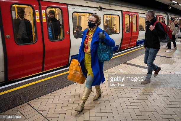 Commuter wears a face-mask as she prepares to travel on an underground train, despite Government recommendations that people avoid social contact...