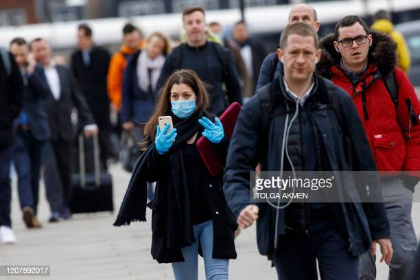 Commuter wears a mask and gloves whilst walking across London Bridge into the City of London during the morning rush hour on March 18, 2020 as people...