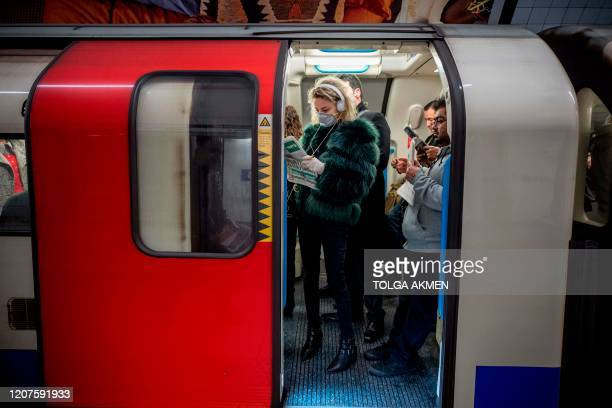 TOPSHOT A commuter wears a mask as a precaution whilst travelling on a London Underground metro train in the morning in central London on March 18...