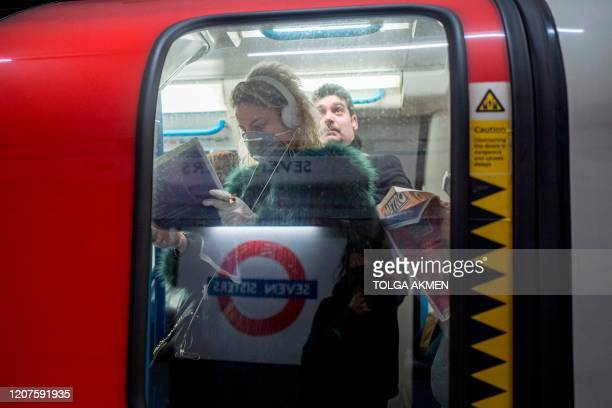 A commuter wears a mask as a precaution whilst travelling on a London Underground metro train in the morning in central London on March 18 2020 as...