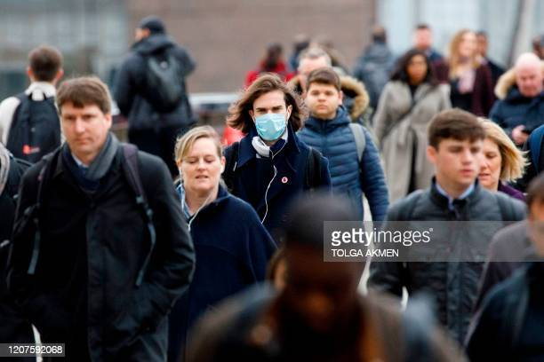 Commuter wears a mask whilst walking across London Bridge into the City of London during the morning rush hour on March 18, 2020 as people take...