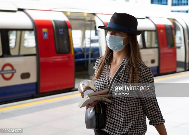 A commuter wears a protective face mask at Stratford station in London England on June 15th 2020 The Government enforced a new law which makes it...