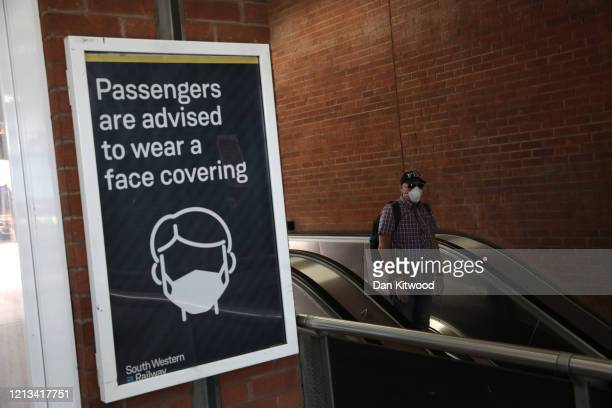 A commuter wears a protective face mask at Waterloo station on May 18 2020 in London England The British government has started easing the lockdown...