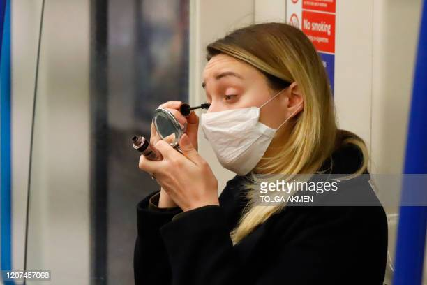 A commuter wears a protective mask as she applies her makeup whilst travelling on the metro train in central London on March 17 2020 Britain stepped...