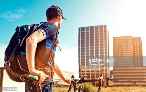 Commuter with backpack holds on to racing bicycle and looks at office buildings