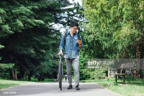 commuter with bike using smartphone - mobile phone stock pictures, royalty-free photos & images
