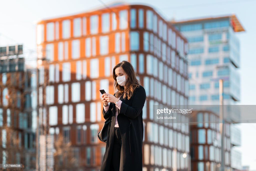 Forens met medisch gezichtsmasker dat haar slimme telefoon gebruikt : Stockfoto