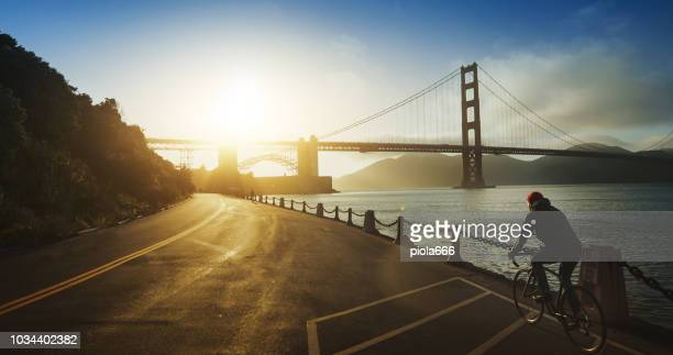 commuter with road racing bicycle and golden gate bridge - san francisco california stock photos and pictures