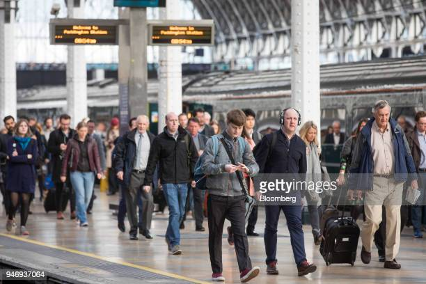 Commuters alight from a Great Western Railway train operated by FirstGroup Plc after arriving at London Paddington railway station in London UK on...