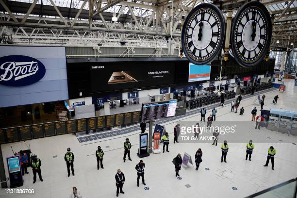 Commuters and employees take part in a minute's silence on the first anniversary of the first national Covid-19 lockdown, at Waterloo Station in...