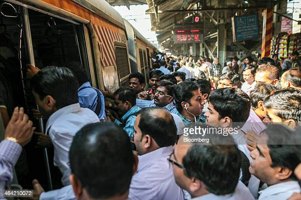 Commuters and passengers board a train at a railway platform at Kurla railway station in Mumbai India on Saturday Feb 21 2015 Indian Railways is...
