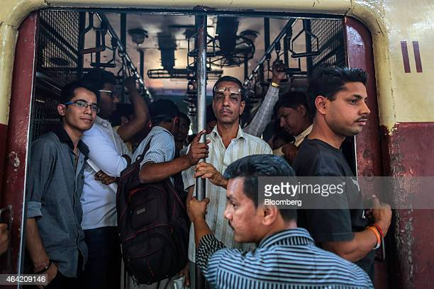 Commuters and passengers on train wait to depart from a railway platform at Parel railway station in Mumbai India on Saturday Feb 21 2015 Indian...
