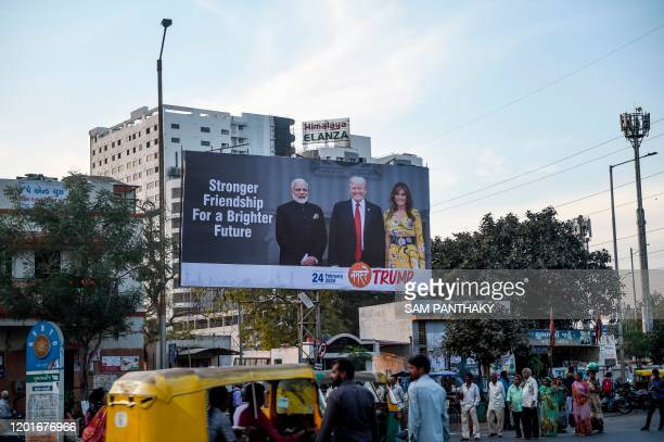 Commuters and pedestrians pass below a billboard depicting US President Donald Trump his wife Melania Trump and India's Prime Minister Narendra Modi...