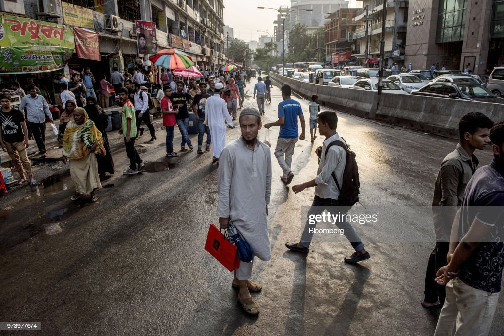 Commuters and pedestrians walk along a road in the Gulshan area of Dhaka, Bangladesh, on Wednesday, June 6, 2018. The Bangladesh economy will expand 6.9% this financial year and 6.8% in 2019, according to asurveyconducted by Bloomberg News. Photographer: Ismail Ferdous/Bloomberg via Getty Images