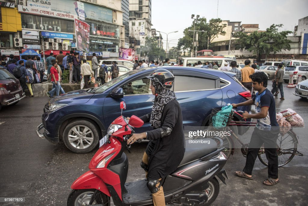 Commuters and pedestrians walk between traffic while crossing a road in the Gulshan area of Dhaka, Bangladesh, on Wednesday, June 6, 2018. The Bangladesh economy will expand 6.9% this financial year and 6.8% in 2019, according to asurveyconducted by Bloomberg News. Photographer: Ismail Ferdous/Bloomberg via Getty Images