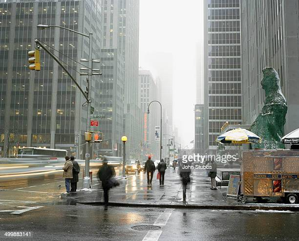 CONTENT] Commuters and pedestrians walking along the Avenue of the Americas Mid Manhattan with snow and rain showers in the air Large grey...