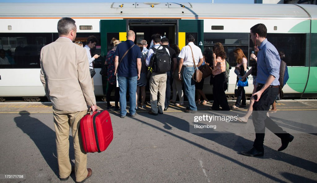 Commuters and rail travelers board a rush hour passenger train operated by Southern Railway Ltd., before departing from Clapham Junction station in London, U.K., on Tuesday, July 9, 2013. U.K. Prime Minister David Cameron is committed to the building of a high-speed rail line linking London to northern England, his spokesman said as evidence mounts that all-party support for the project is fracturing. Photographer: Simon Dawson/Bloomberg via Getty Images