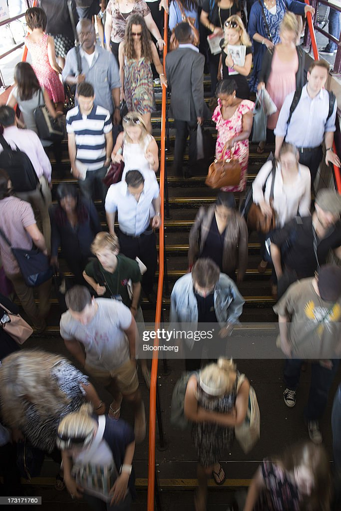 Commuters and rail travelers descend stairs as they exit the platform at Clapham Junction train station in London, U.K., on Tuesday, July 9, 2013. U.K. Prime Minister David Cameron is committed to the building of a high-speed rail line linking London to northern England, his spokesman said as evidence mounts that all-party support for the project is fracturing. Photographer: Simon Dawson/Bloomberg via Getty Images