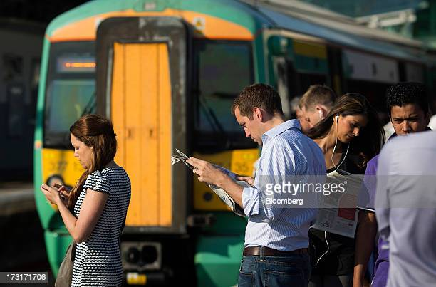 Commuters and rail travelers read newspapers and use mobile devices as a passenger train operated by Southern Railway Ltd approaches Clapham Junction...