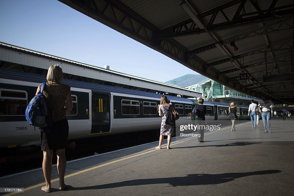 Commuters and rail travelers wait for a passenger train to arrive at a platform before departing from Clapham Junction station in London, U.K., on Tuesday, July 9, 2013. U.K. Prime Minister David Cameron is committed to the building of a high-speed rail line linking London to northern England, his spokesman said as evidence mounts that all-party support for the project is fracturing. Photographer: Simon Dawson/Bloomberg via Getty Images
