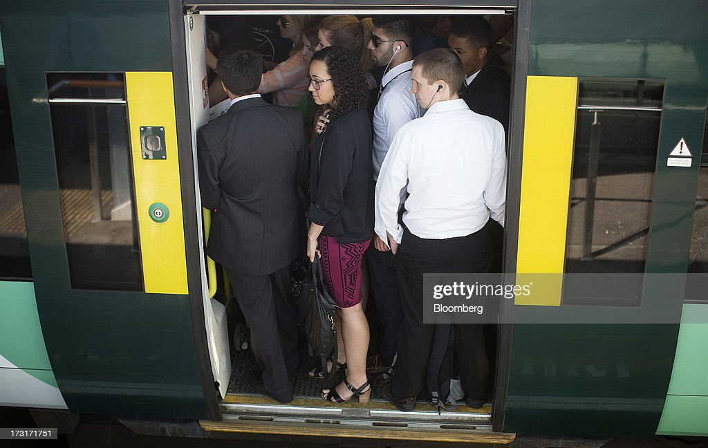 Commuters and rail travelers wait for the doors of a rush hour passenger train operated by Southern Railway Ltd., to close before departing from Clapham Junction station in London, U.K., on Tuesday, July 9, 2013. U.K. Prime Minister David Cameron is committed to the building of a high-speed rail line linking London to northern England, his spokesman said as evidence mounts that all-party support for the project is fracturing. Photographer: Simon Dawson/Bloomberg via Getty Images