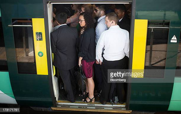 Commuters and rail travelers wait for the doors of a rush hour passenger train operated by Southern Railway Ltd to close before departing from...