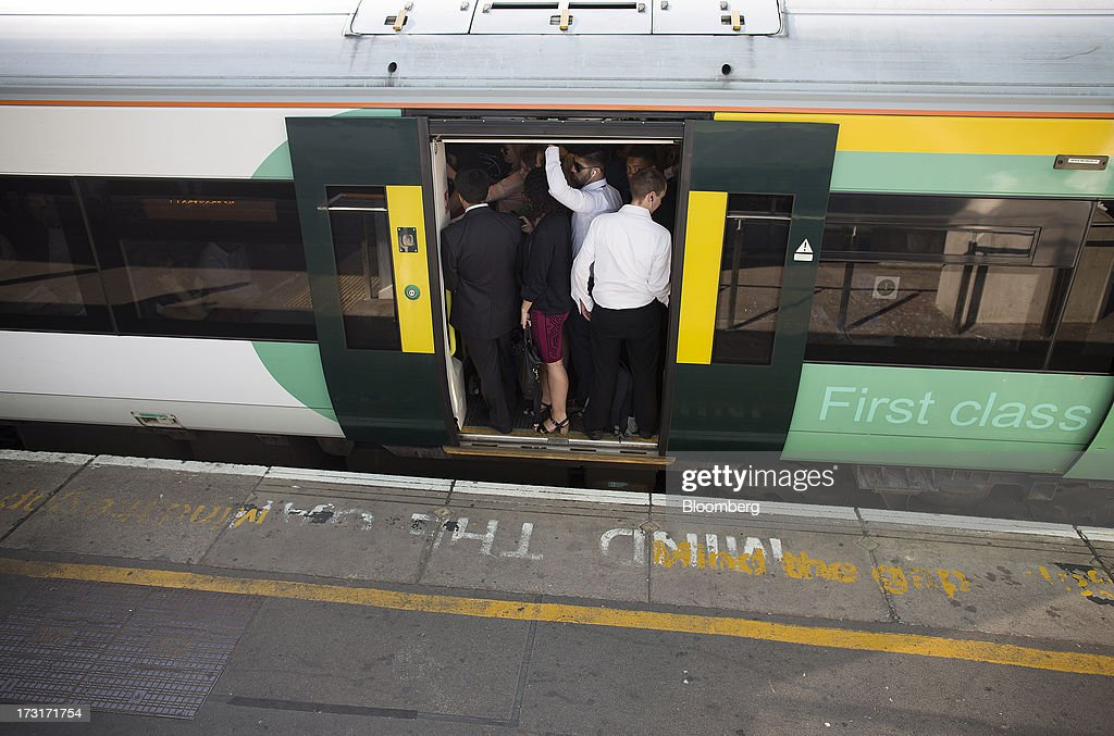Commuters and rail travelers wait for the doors of a rush hour passenger train, operated by Southern Railway Ltd., to close before departing from Clapham Junction station in London, U.K., on Tuesday, July 9, 2013. U.K. Prime Minister David Cameron is committed to the building of a high-speed rail line linking London to northern England, his spokesman said as evidence mounts that all-party support for the project is fracturing. Photographer: Simon Dawson/Bloomberg via Getty Images