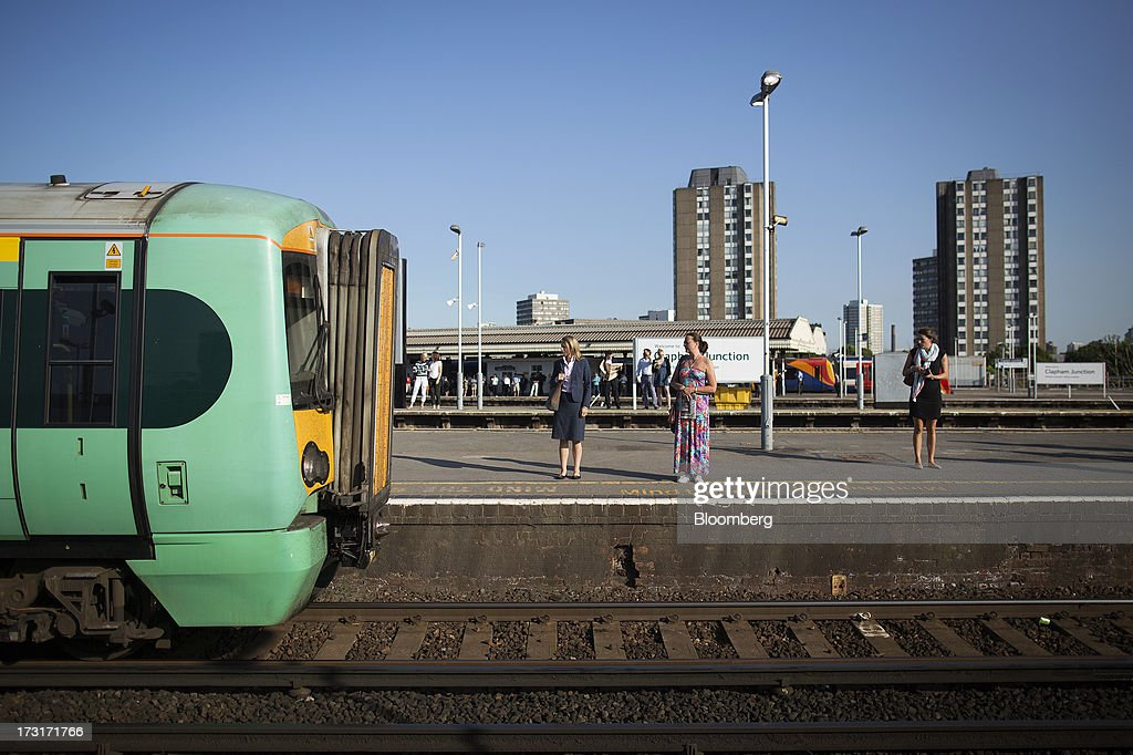Commuters and rail travelers wait on a platform as a passenger train, operated by Southern Railway Ltd., arrives at Clapham Junction station in London, U.K., on Tuesday, July 9, 2013. U.K. Prime Minister David Cameron is committed to the building of a high-speed rail line linking London to northern England, his spokesman said as evidence mounts that all-party support for the project is fracturing. Photographer: Simon Dawson/Bloomberg via Getty Images