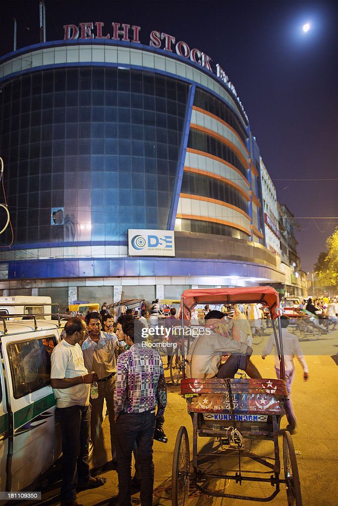 Commuters and rickshaw drivers gather in front of the Delhi Stock Exchange Ltd. building in New Delhi, India, on Wednesday, Sept. 18, 2013. The Federal Reserves decision to postpone its rollback of U.S. stimulus offered Asian policy makers extra time to address domestic economic fragilities as the region copes with diminished capital inflows. Photographer: Prashanth Vishwanathan/Bloomberg via Getty Images