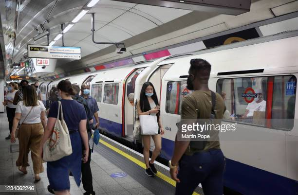 Commuters and shoppers opt to continue wearing face coverings on the London Underground system despite it no longer being enforced on July 19, 2021...