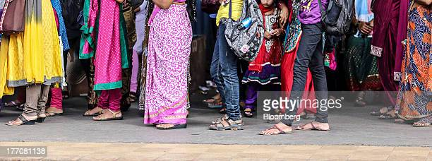 Commuters and travelers wait for a train at Sandhurst Road Railway Station during the morning rush hour in Mumbai India on Tuesday Aug 20 2013 Indias...