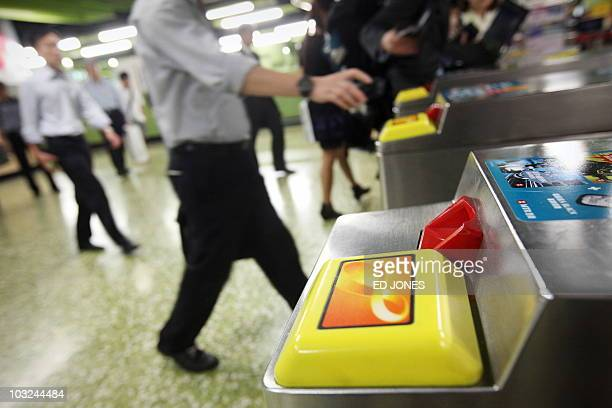 Commuters approach 'Octopus' storedvalue card readers positioned at exit turnstiles at a mass transit railway station in the Wanchai district of Hong...