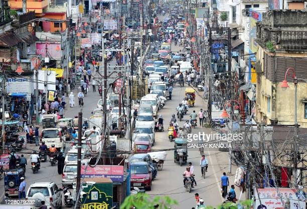 Commuters are seen along a road in the old neighbourhood of Chowk, in Allahabad on August 17, 2020. - India's official coronavirus death toll soared...