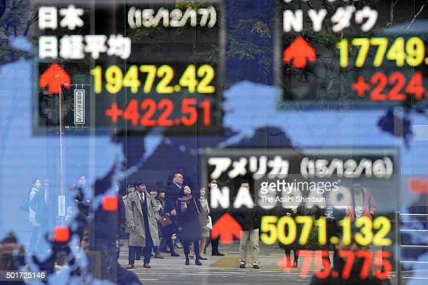 Commuters are seen reflecting on an electric board displaying the Nikkei 225 a day after the US Fereral Reserve announced it will raise the interest...