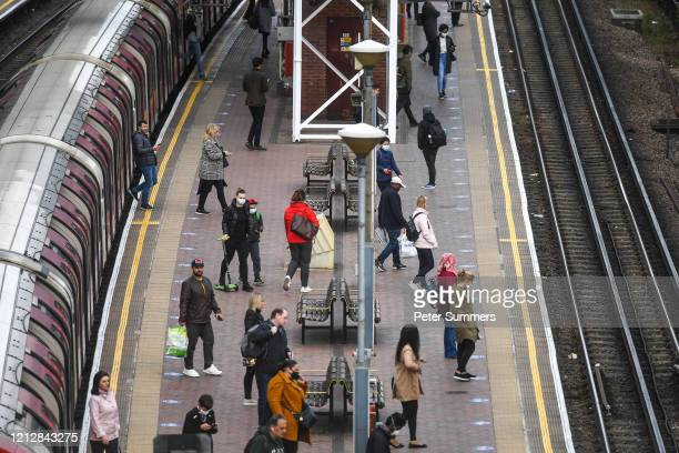 Commuters are seen waiting to board a tube train at North Acton station on May 13, 2020 in London, England. The prime minister announced the general...