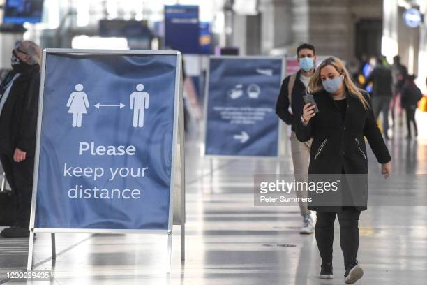 Commuters are seen wearing face coverings at Waterloo train station on December 20, 2020 in London, England. London and large parts of southern...