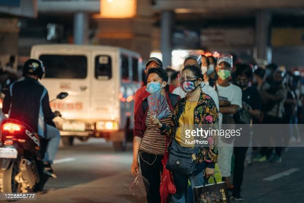 Commuters are seen wearing face masks and face shields as they queue to board a bus, amid the coronavirus disease outbreak on October 1 in Quiapo,...