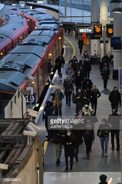 Commuters arrive at Waterloo station during the morning rush hour as Britain enters a national lockdown in London on January 5, 2021. - Britain...
