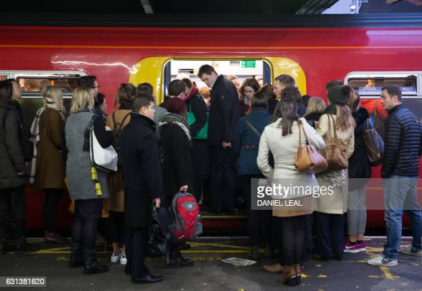 Commuters attempt to board a full Southwest Train carriage toward central London at Clapham Junction station in London on January 10 2017 after...