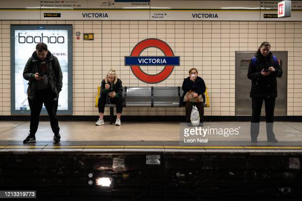 Commuters attempt to keep some distance between each other before boarding an underground train as the Government recommends that people avoid social...