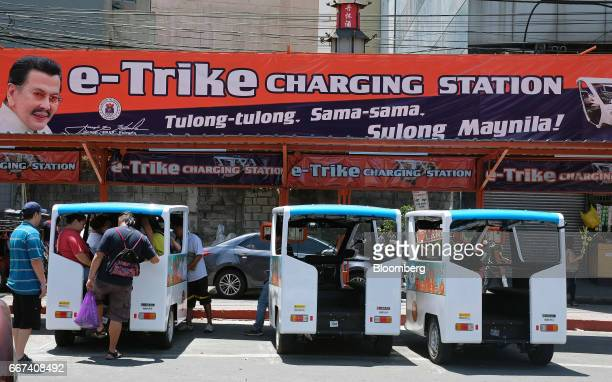 Commuters board a Bemac Electric Transportation Philippines Inc ETrike electric tricycle below a banner featuring an image of Joseph Estrada mayor of...