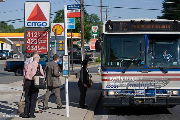 Commuters board a bus near gas stations in Bethesda Maryland Mass transit ridership is rising nationally due to the recent rise in gas prices