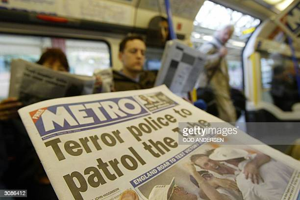 Commuters board a Picadilly line train at London's Barons Court station as fellow passengers read about stepped up security measures 15 March 2004...