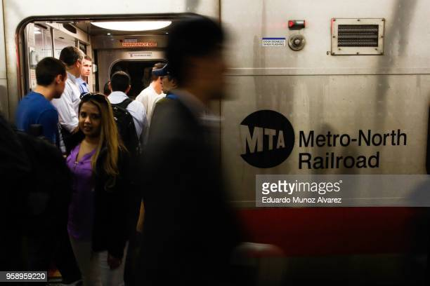 Commuters board a train as they wait for service to be restored after a severe thunderstorm downed trees that caused power outages resulting in...