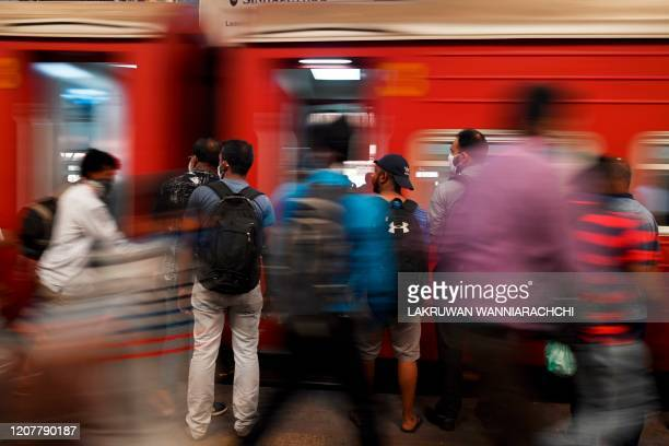 Commuters board a train at a railway station after the authorities announced a weekend curfew in the country as a preventive measure against the...
