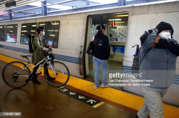 Commuters board a train at the MacArthur BART station in Oakland, Calif. On Tuesday, May 12, 2020. BART is joining transit agencies from around the...