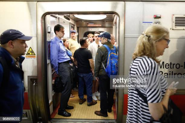 Commuters board trains as they wait for train service to be restored after a severe thunderstorm downed trees that caused power outages resulting in...