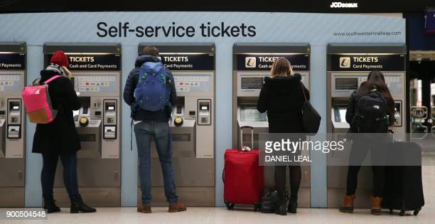 Commuters buy rail tickets at a self-service machine at Waterloo station, in central London on January 2, 2018. - As the price of an average ticket...
