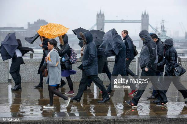 Commuters carrying umbrellas to shelter from the rain battle against high winds as they cross London Bridge during the approach of the 'Storm Doris'...